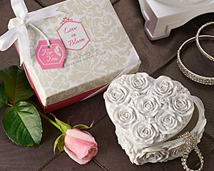 Love in Bloom Heart Jewelry & Trinket Box   Nothing evokes a sense of love and romance like a simple heart shape or the bloom of roses. Artisano Designs? marries both with this fabulous jewelry/trinket box sure to be a bridal shower and wedding party favorite! In amazing detail and white finish, the heart bursts with a rose floral expression that is sure to take your guests breath away.  Features:    Gorgeous gift packaging with pink base and ?Love in Bloom? patterned theme top Completed with satin white ribbon and bow and includes matching ?For You? gift tagMade of weighty sculpted resin with white finish  A perfect keepsake favor for Valentine?s Day, birthdays or any special event Jewel box measures approx. 3.5? x 1.75? (9 x 4.5 cm) Gift box measures approx. 3.75? x 3.75? x 2? (9.5 x 9.5 x 5 cm)
